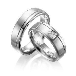 Couple d'alliances en or blanc brossé et diamant taillé en coeur